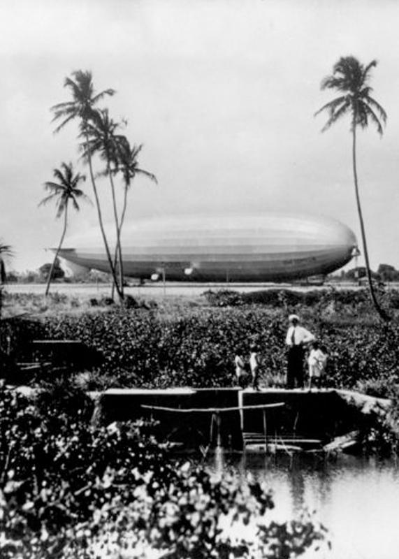 Foto des Luftschiffes LZ127, dass den Kapitän vor dem Schiff unter Palmen zeigt.