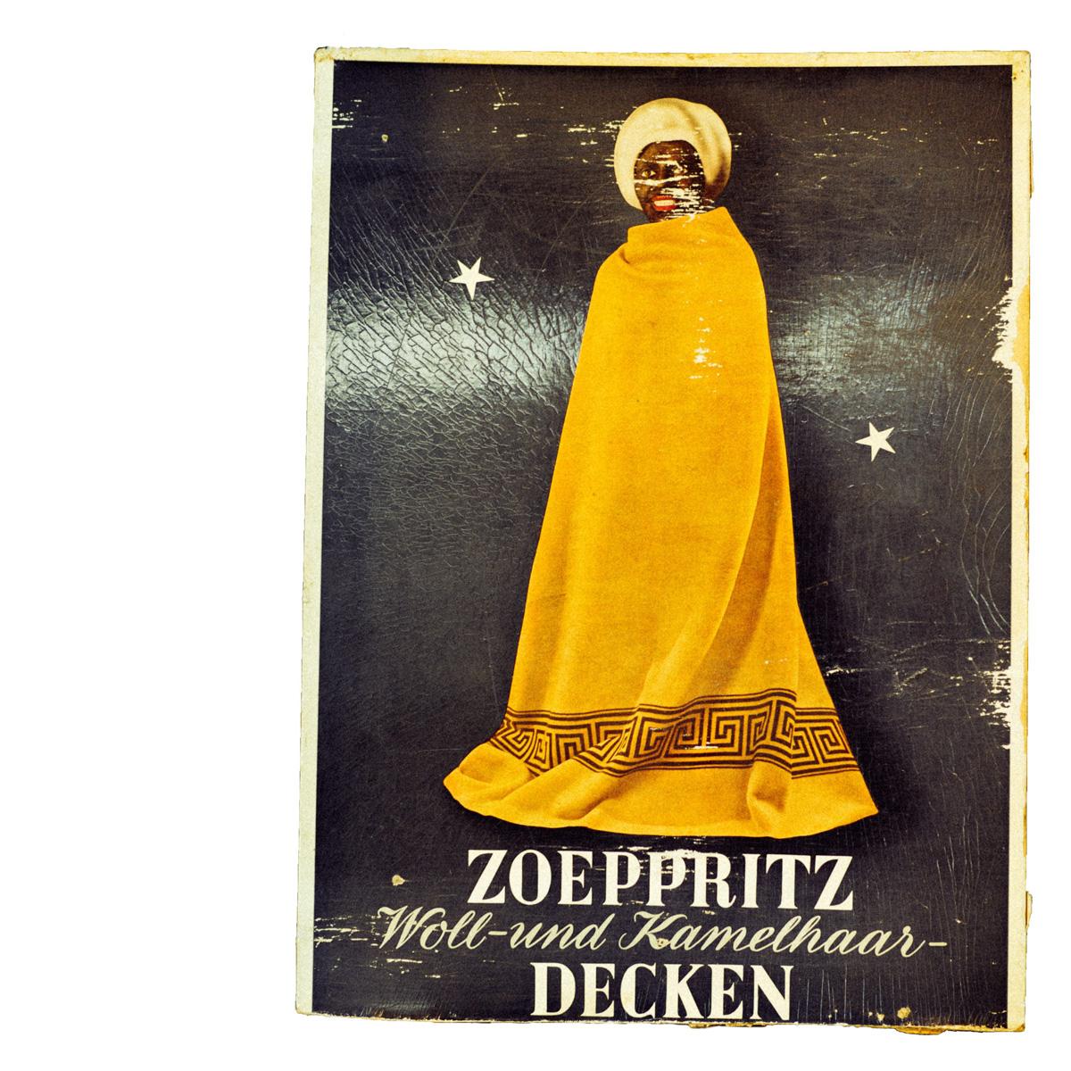 Scan eines alten Aufstellers der einen in eine zoeppritz Decke gehüllten Mohr zeigt.