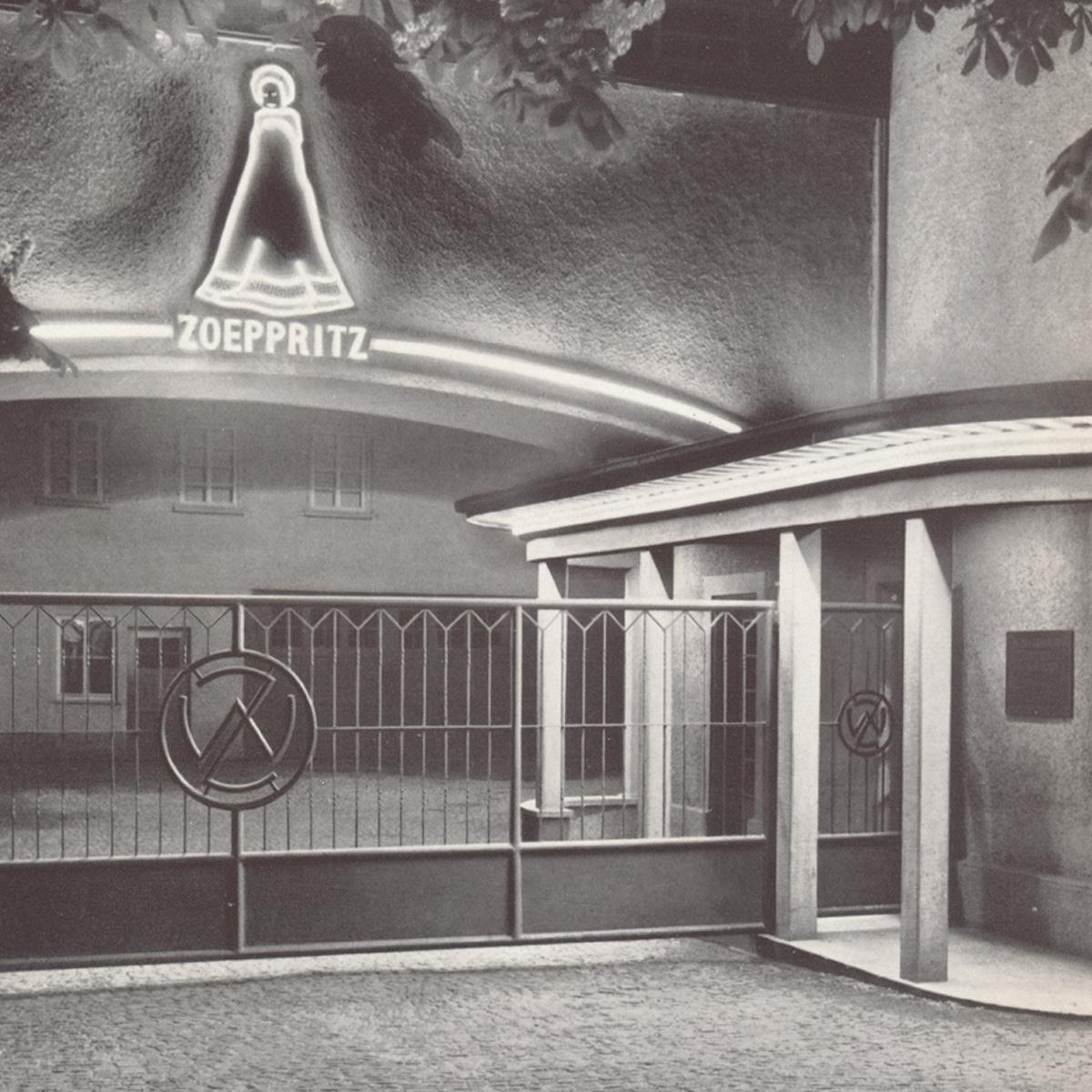 nächtliche Szene des bleuchteten Eingangsbereichs des zoeppritz Werkes um 1953