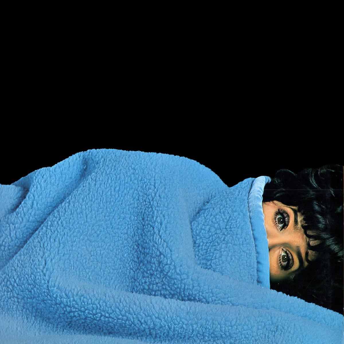 Das Katalog-Cover zeigt eine Frau, die bis zu den Augen unter einer blauen Wohndecke liegt.
